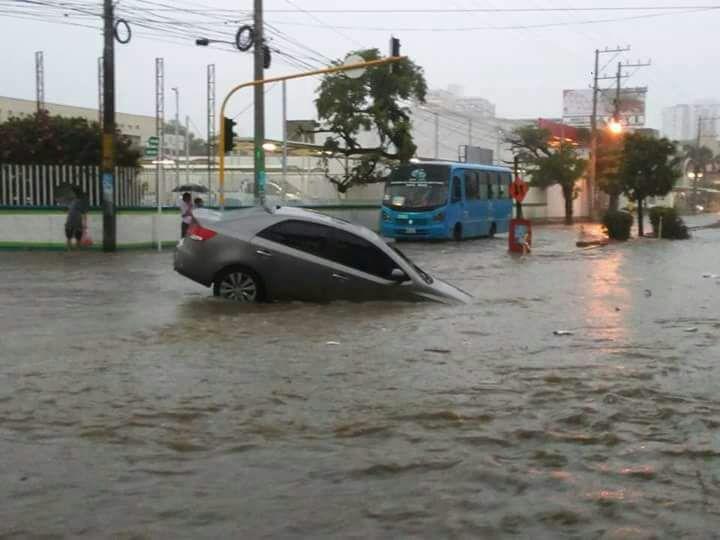 El carro quedó atascado en la mitad de la vía inundada.