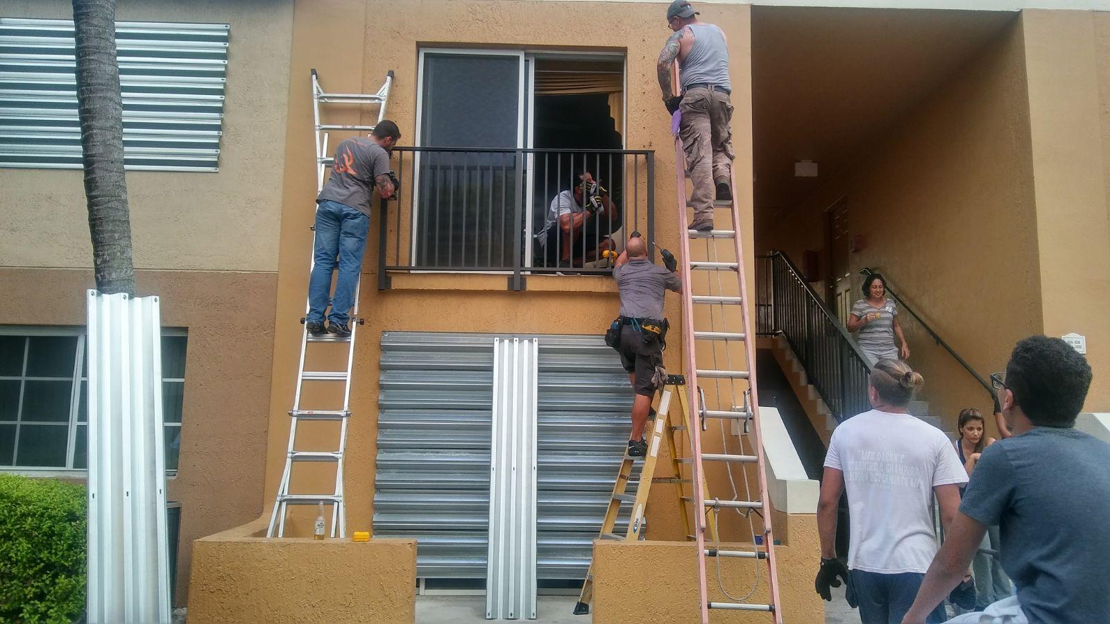 Los residentes de los apartamentos instalan protectores para las ventanas.