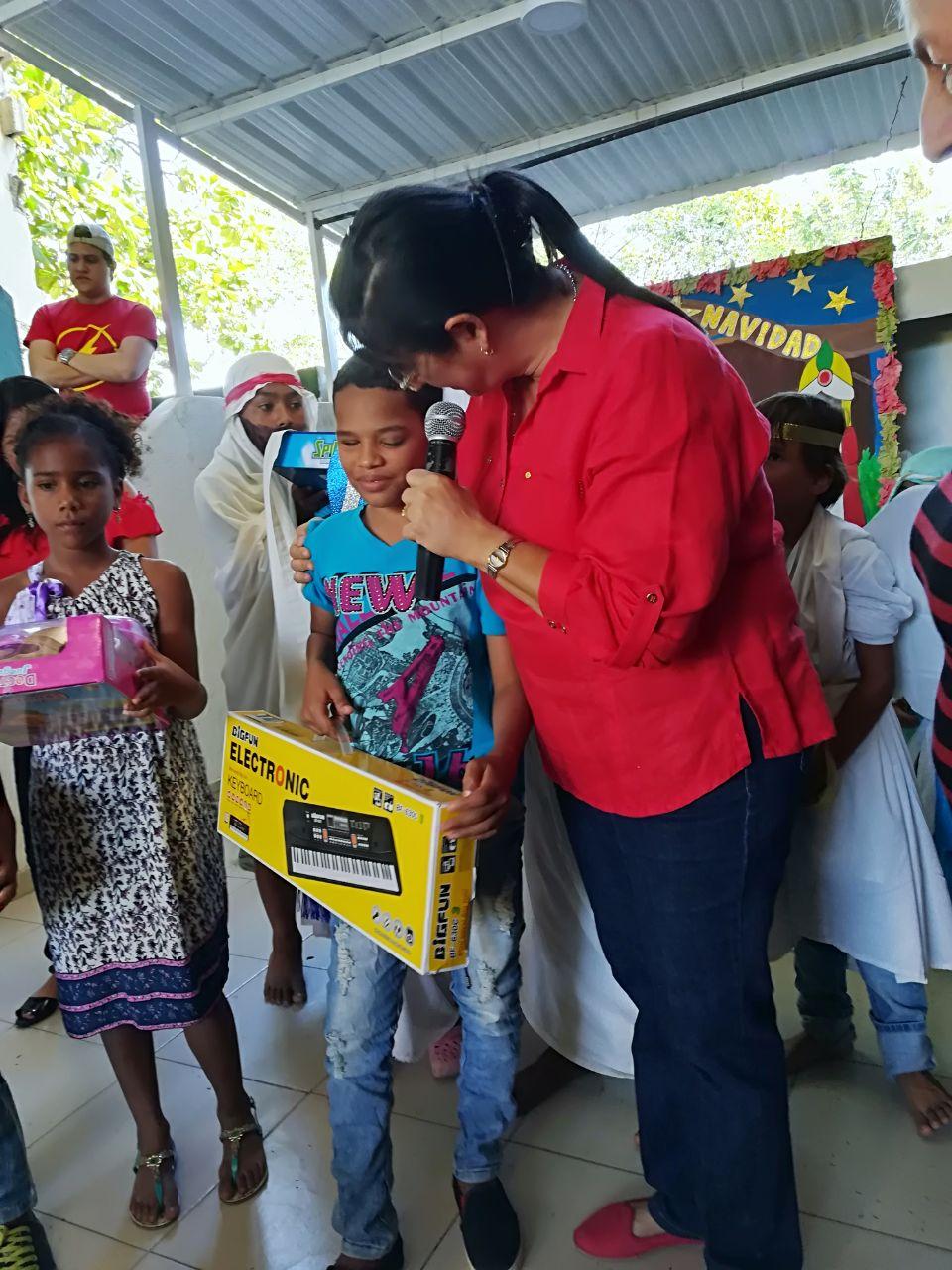 Mónica Salas, mujer que conducía el vehículo accidentado, entregando regalos a niños de escasos recursos.
