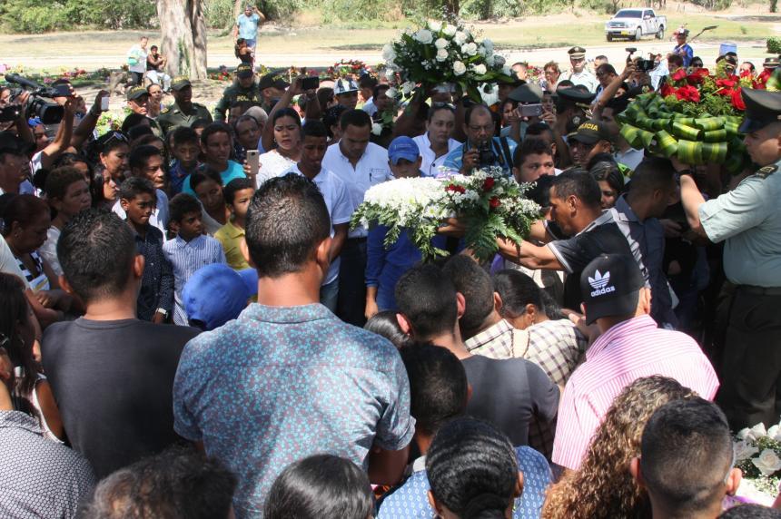 José Aurelio Rada sostiene la corona de rosas durante el sepelio de su hijo.