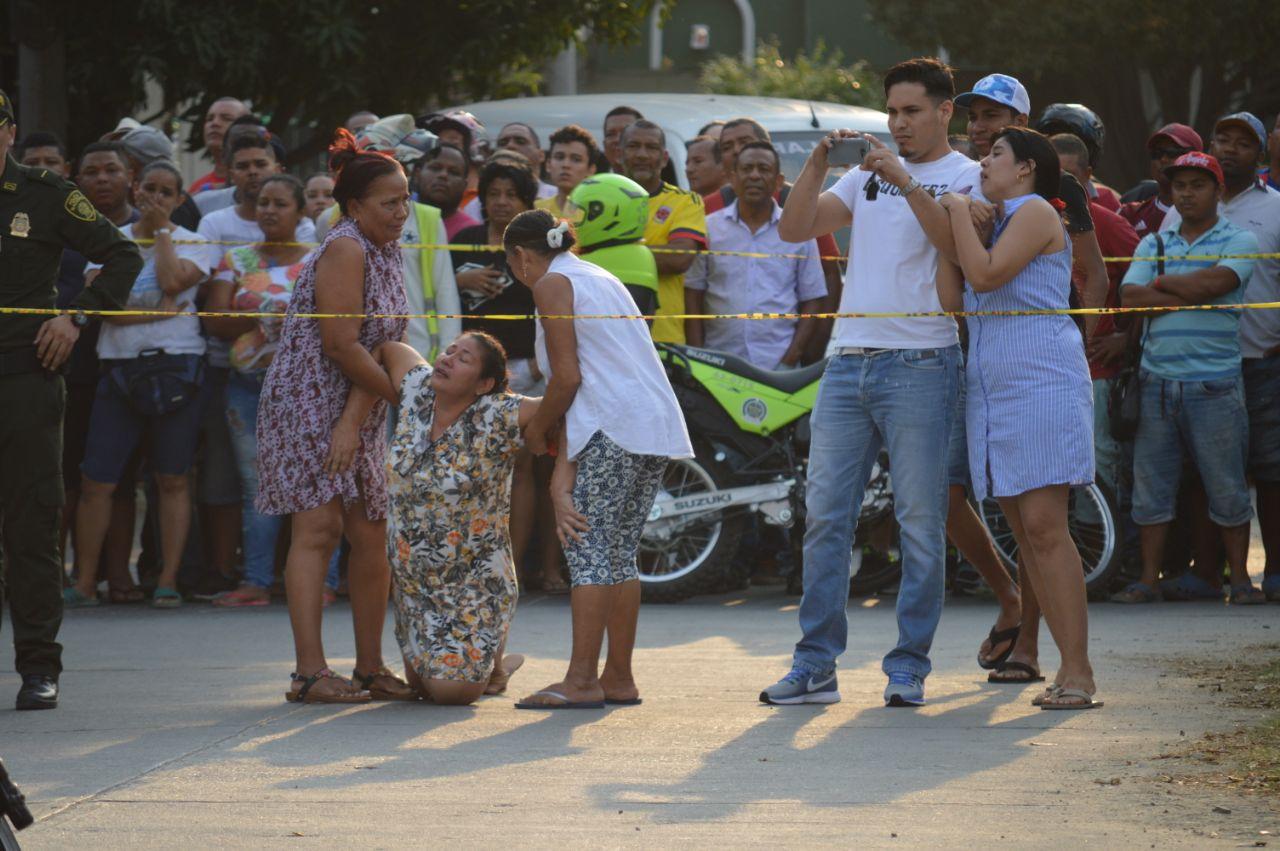 Madre del hombre asesinado llora desconsolada al llegar al sitio del crimen.