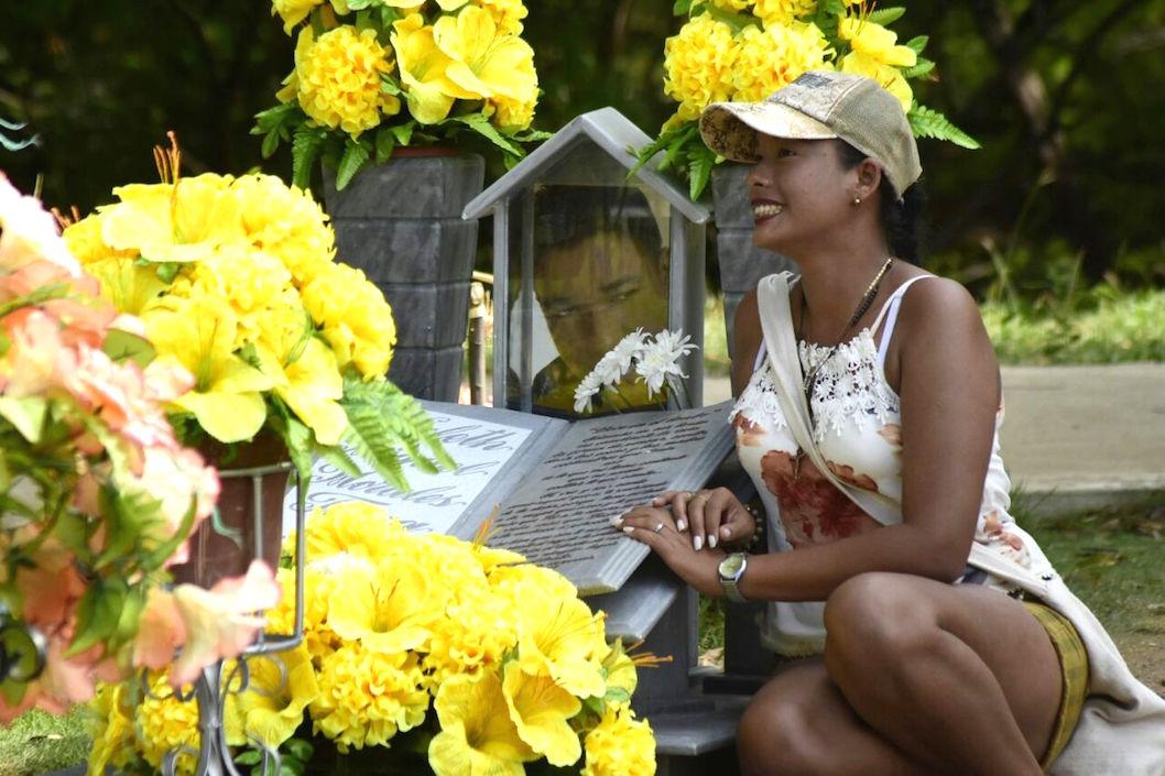 Una fanática posando frente a la tumba.
