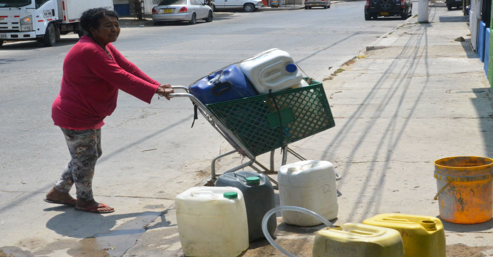 Hombres y mujeres se ven por las calles de Pescaíto cargando agua en pimpinas.