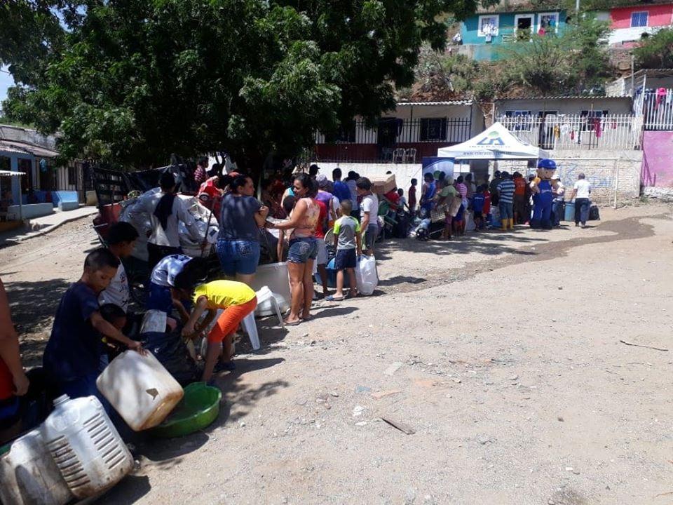 Las personas hacen filas con productos reciclables para adquirir productos de las ecotiendas.