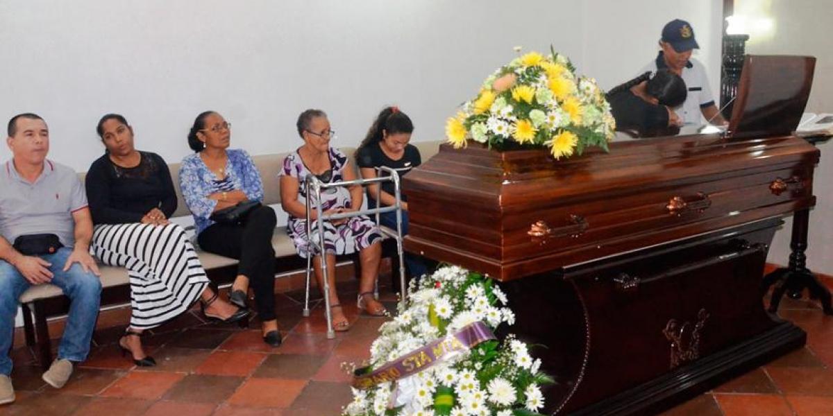 Féretro donde se encontraba el cuerpo de Rafael Viloria. Su hermano Zacarías llora mientras lo observa.