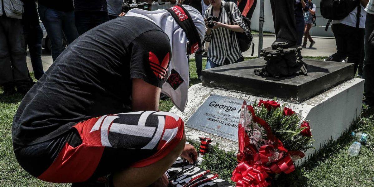Un hombre pone flores en homenaje a las víctimas del incendio registrado en la madrugada de este viernes, en el centro de entrenamiento del club de fútbol Flamengo.