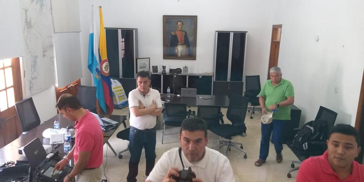 A la derecha, de rojo, Emiro Castro acompañado por otras 4 personas, mientras hacen revisiones de los discos duros.