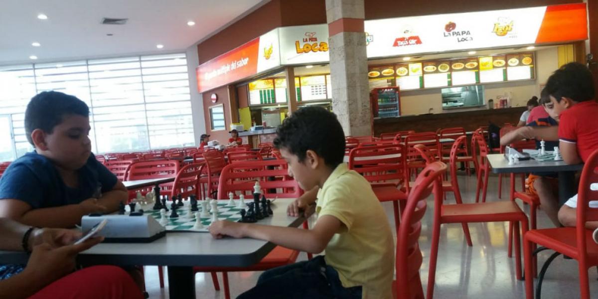 En la foto se ven las mesas vacías mientras los niños juegan ajedrez.
