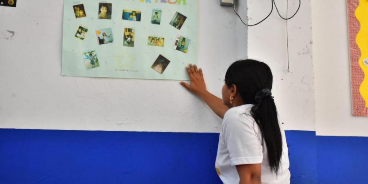 La profesora Shirley Pardo observa la cartelera de reconocimiento a María José.