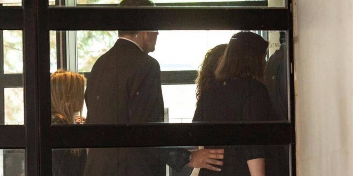 La cantante Shakira (al fondo, tapada) ha eludido este jueves a la prensa que la esperaba a las puertas del juzgado de Esplugues.