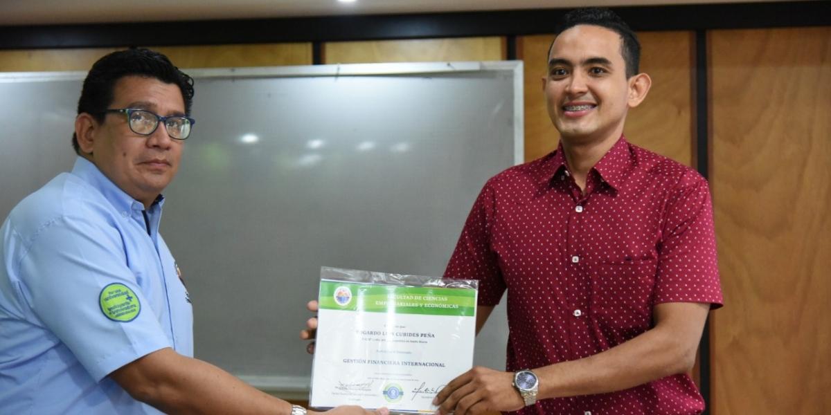 Fernando Clavijo Santana, director del Programa de Contaduría Pública, entregando uno de los certificados.