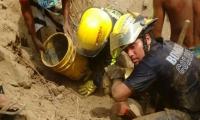 Socorristas tratando de rescatar el cuerpo con la ayuda de la comunidad.