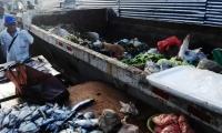 Los alimentos se vende al lado de un contenedor de basura.