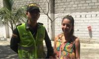El patrullero Jean Romero (izq) junto a la joven que perdió y recuperó su dinero.