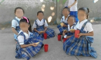 Las niñas reciben los alimentos en el piso.