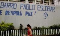 Una niña camina frente al mural que da la bienvenida al barrio Pablo Escobar en Medellín.