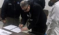Exjefe paramilitar Daniel Rendón Herrera firmado documentos durante su extradición.