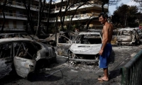 Un residente observa el estado en que han quedado varios coches calcinados tras el paso de las llamas por Mati, barrio del noreste de Atenas (Grecia) .