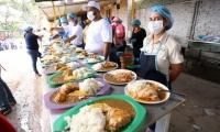 Voluntarios esperan con comidas calientes a los beneficiarios que llegan diariamente.