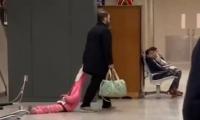 Padre arrastrando a su hija en aeropuerto de Estados Unidos.