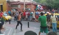 Momento en que una de las personas del establecimiento comercial peleaba con el hombre de la calle (de verde).