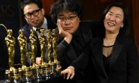 El director coreano Bong Joon Ho, viendo las estatuillas obtenidas por su película 'Parasite'