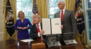 Donald Trump junto a Kirstjen Nielsen y Mike Pence al momento de firmar la orden ejecutiva.