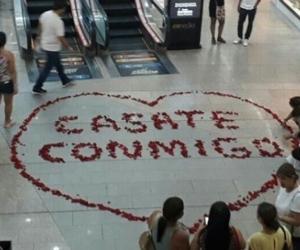 El joven le dio el mensaje con pétalos de rosa en el medio del centro comercial.