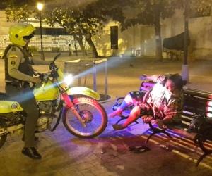 Momento en que el policía despierta a una mujer indigente y le pide que se vaya a otro lado.