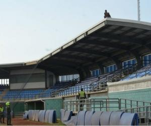 Hombre subido en el techo del estadio de beisbol.