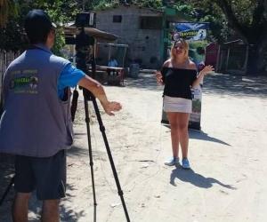 Daniela Salom, presentando para Travesía TV, medio de Gustavo Durán (de espaldas), quien la habría engañado y le niega el pago por su labor.