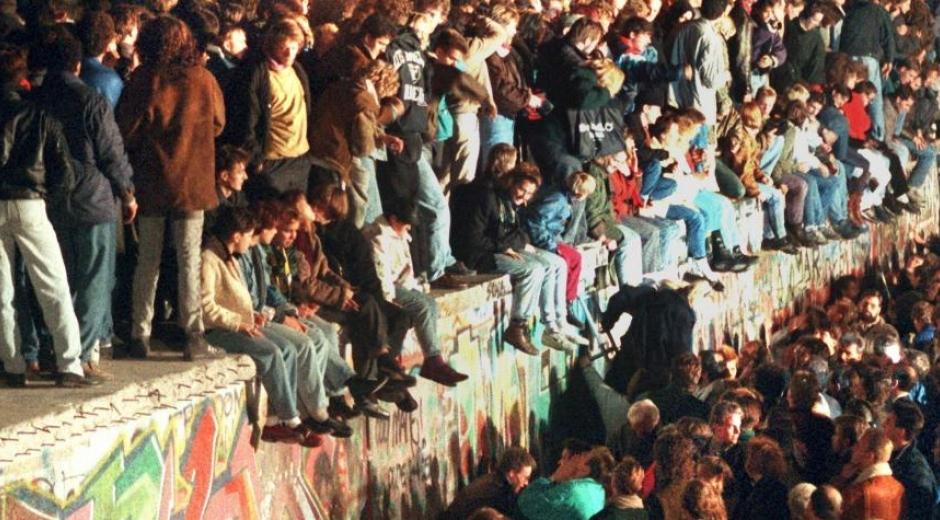 Jóvenes sobre el Muro de Berlín.