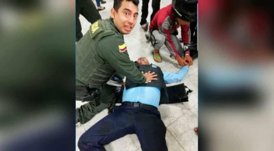 Momento en que patrullero y joven auxilian a vigilante atacado a bala.