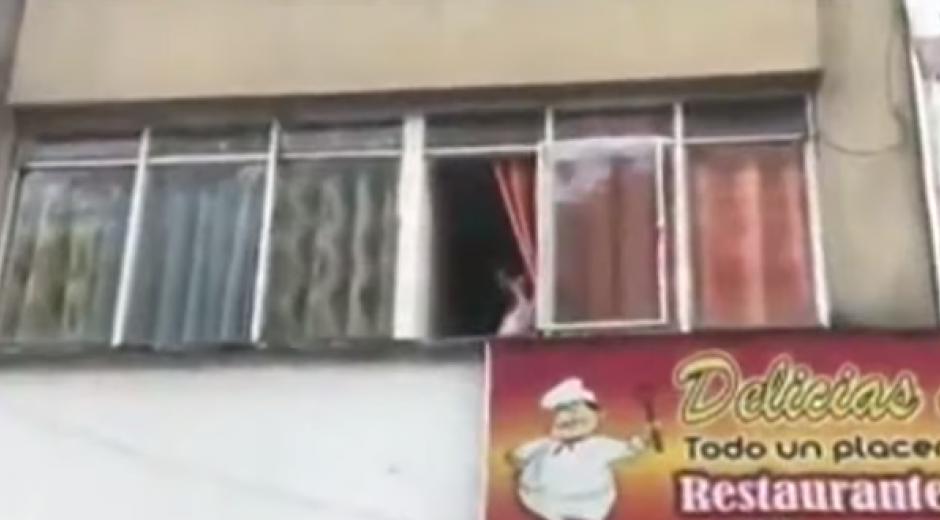 Mujer lanza billetes desde su ventana