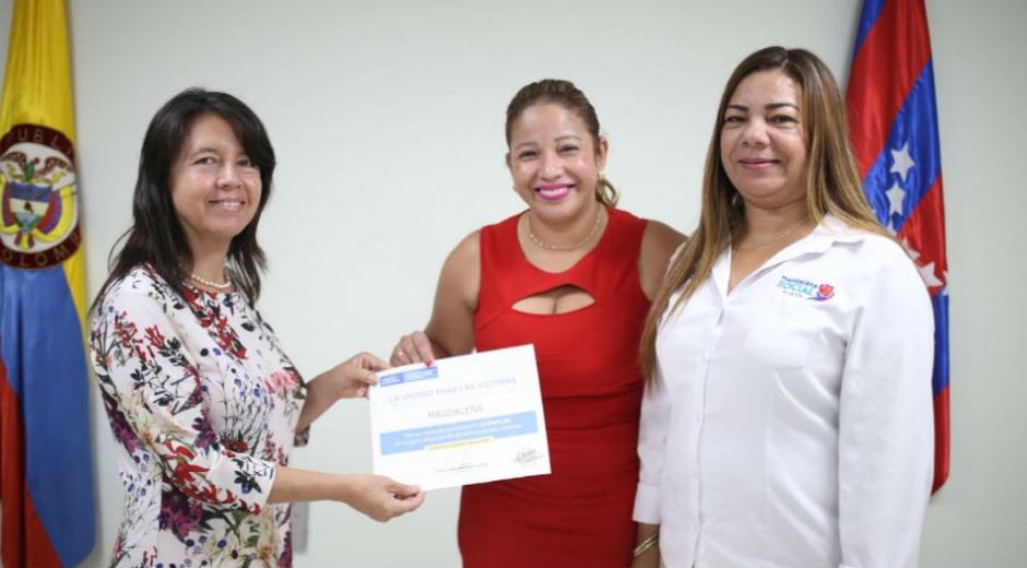Norma Vera recibiendo el reconocimiento entregado por la Unidad de Víctimas.