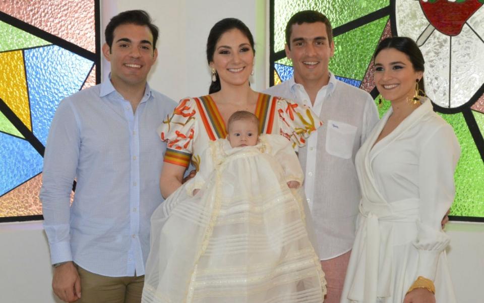 El bebé en compañía de sus padres y demás familiares.